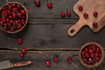 Wooden empty background with cherry berries and plates full of cherry
