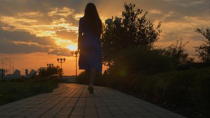Girl walking away through park at the sunset. Slide.