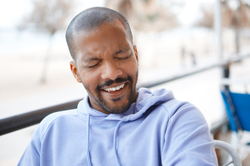 Closeup portrait of happy confident young African-American man hipster in sport hoody smiling.Blurred city on background.