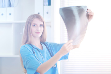 Young female doctor looking at the x-ray picture