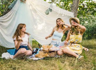 Group of girls friends making picnic outdoor. They have fun.