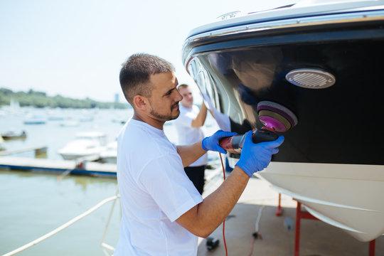 Boat maintenance - Man with orbital polisher polishing boat in marina. Selective focus.