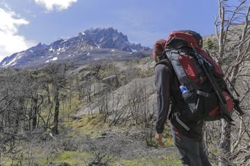 Homem com mochila cargueira observando as montanhas durante caminhada.