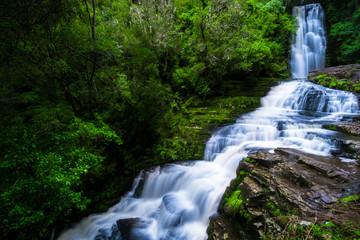 Long Exposure photography. Beautiful waterfall in the rainforest with green nature. Purakaunui Falls, The Catlins, New Zealand.