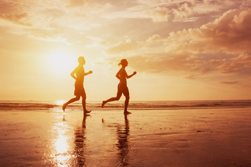 Silhouette of two runners people jogging on sunset sea beach. Healthy lifestyle background with copyspace. Family leisure activities, sport and workout. Man and woman running.