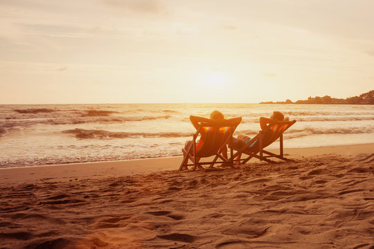 Tourism and travel vacation. Senior happy couple relaxing in luxurious resort sunset beach in deck chairs. Romantic honeymoon holidays. Recreation concept with copyspace.