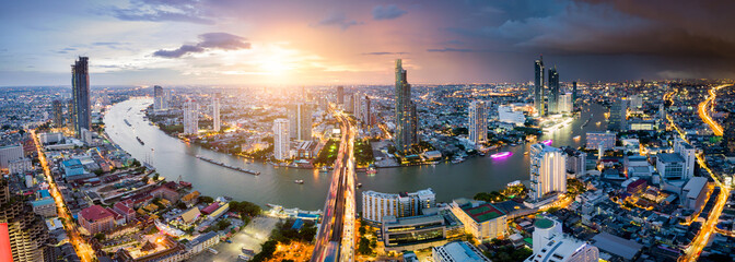 Aerial view of Bangkok skyline and skyscraper with light trails on Sathorn Road center of business in Bangkok downtown. Panorama of Taksin Bridge over Chao Phraya River Bangkok Thailand at sunset. Wall mural