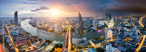 Wall mural Aerial view of Bangkok skyline and skyscraper with light trails on Sathorn Road center of business in Bangkok downtown. Panorama of Taksin Bridge over Chao Phraya River Bangkok Thailand at sunset.