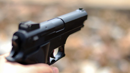 Close-up image of gun on the blur background.