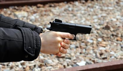A woman's hand pointing a gun.