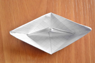 Origami a paper ship from a white empty blank sheet in a cage on wooden table. Top view