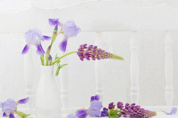 blue flowers in vase on white wooden shelf