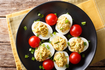 Boiled stuffed eggs with tuna and avocado with tomatoes and green onions close-up on a plate. horizontal top view