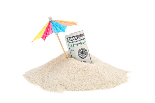 Rolled up money with beach umbrella on the heap of sand. Isolated on white.