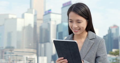 Business woman use of tablet computer in city