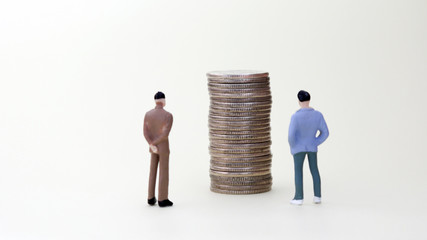 Two miniature men looking at a pile of coins.