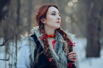 Beautiful girl with long braids in a winter forest. A witch from a fairy tale. fantasy Photo