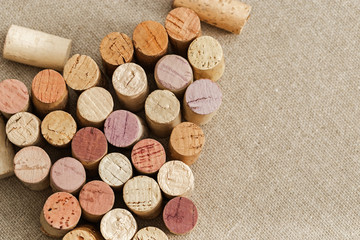 Used wine corks on sackcloth background with empty space for text. Colorful corks from white and red wine bottles. Top view.