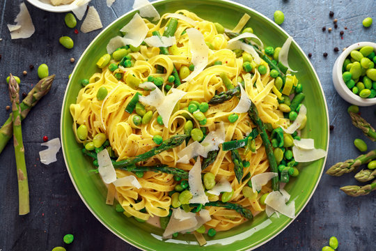 Pasta tagliatelle with asparagus, peas, beans and parmesan cheese on top. healthy food