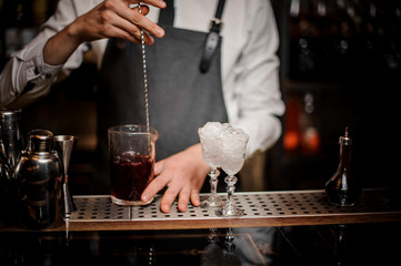 Bartender stirring fresh alcoholic cocktail in glass