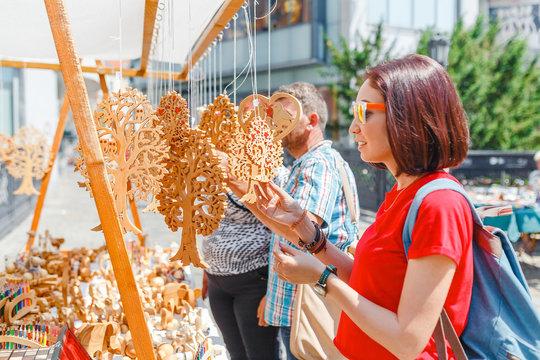 A woman tourist at a souvenir fair choosing handmade decorative woodcarving gifts