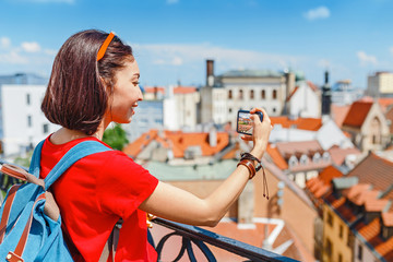 Young woman taking a photo on her smartphone in Europe