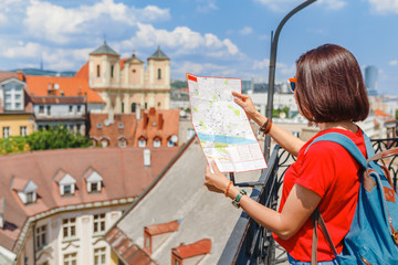 A young happy girl traveler looks at the map and tries to find the right direction for the next attraction in the European city