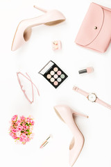 Fashion blogger workspace flat lay with pumps, cosmetics, purse, planner book and flowers.