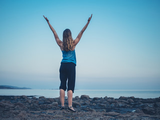 Woman raising arms on coast