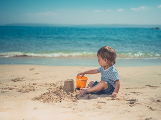 Toddler on beach building sand castle