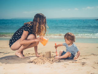 Young mother playing with son on beach