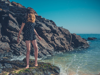 Woman standing on rocks by the waves