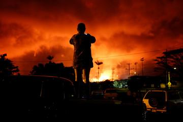 A woman takes a photo as lava lights up the sky above Pahoa