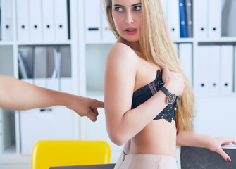 Man's hand pulls bra out of the beauitiful secretary in office background. Flirt or harassment concept.