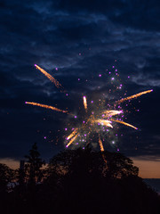 Fireworks in the night sky with clouds at dusk