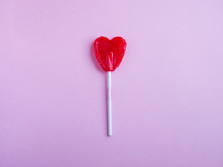 Red heart lollipop on pink background