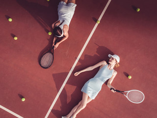 Overhead top view of two young Caucasian teen models wearing fashionable tennis dresses, lying on tennis hardcourt with a lot of balls, summer sunny day outdoors. Fashion portrait shoot