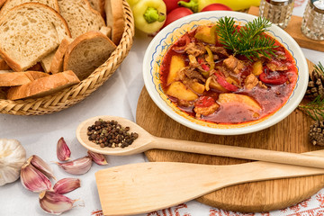 Pot goulash with divas placed on the table of ingredients - meat, pepper, tomato, spices, potatoes, garlic, onion recipe for the preparation of traditional European food