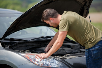 Photo of young man next to broken car with open hood