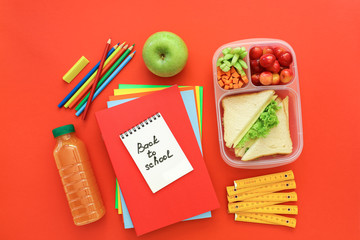 School supplies and lunch box with sandwiches, pieces of cucumbers and carrots, apricot, cherries, apple, bottle of juice on red background, back to school concept.
