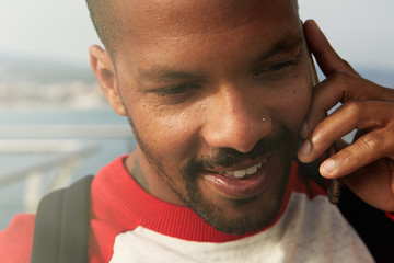 African American man using mobile phone on the beach. Young happy smiling urban hipster man wearing informal clothes and using smart phone