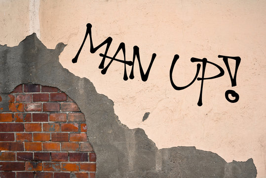 Man Up - Handwritten graffiti sprayed on the wall - motivation and challege to be strong, brave, bold and courageous male instead of being weak and unmanly man.