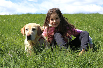 little girl and dog lying on green meadow in the mountains