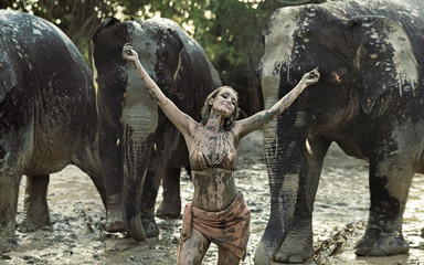 Sensual tamer playing with elephants in mud