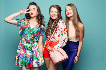Beautiful fashionable girls in bright clothes smiling at camera against azure background.