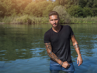 Attractive young athletic man standing in water in sea or lake, wearing black t-shirt