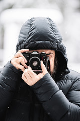 Mann fotografiert mit analoger Kamera im Winter bei Lofer in den Alpen