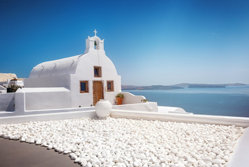Church in Oia, Santorini, Greece, Cyclades. The blue sea in background