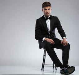 attractive young man wearing a black tuxedo sitting on chair