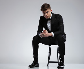 sexy young man in black tuxedo sitting on chair